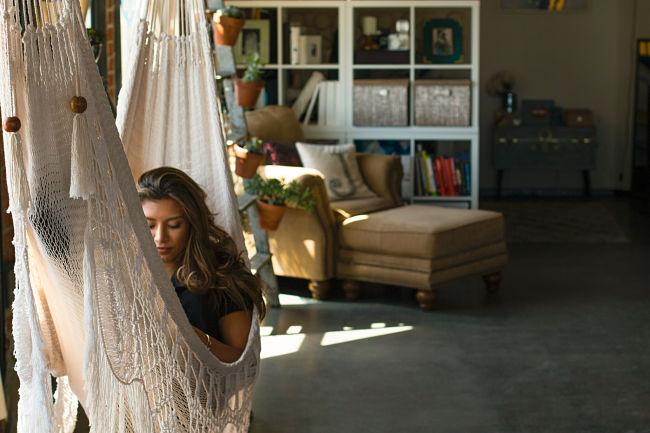 mujer tumbada leyendo en una hamaca de tela